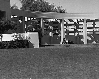 A view of the pergola on the north side of Elm Street in Dealey Plaza in Dallas, Tex., Nov. 22, 1963, moments after shots felled President John F. Kennedy and Texas Gov. John Connally while riding in the presidential motorcade, Nov. 22, 1963. Man with back to camera is Abraham Zapruder with his assistant Marilyn Sitzman beside him. Charles and Beatrice Hester are sitting on the ground.