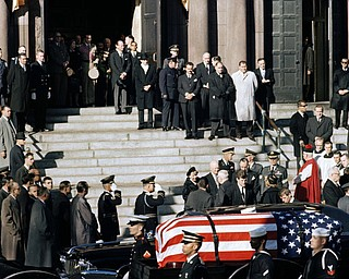 A general view outside St. Matthew's Cathedral in Washington, D.C., during President John F. Kennedy's funeral, with flag-draped coffin in the foreground, Nov. 25, 1963. The president's brothers can be seen behind the casket. At left is Sen. Edward M. Kennedy (D-Mass.), and at right entering limousine is Attorney General Robert F. Kennedy.