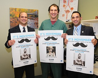 Dr. Dan Ricchiuti, left,  surgical assistant Andrew Labedz, and HMHP Foundation special events/prospect manager Jonathon Fauvie showed off Movember notices from Man Up Mahoning Valley at the Boardman office of NEO Urology.