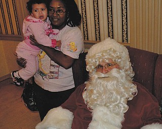 One-year-old Miya Moore, who is held by her godmother, Othella May, refuses to sit on Santa's lap.