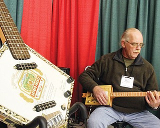 Ed Wentling of Farrell, Pa., demonstrates one of his cigar-box guitars at the Holiday Craft & Gift Show at Eastwood Expo Center in Niles. He has built more than 200 of the instruments that are patterned after guitars from the American southern bayou. His company is called Bayou Blues Guitars. He was at the show, which ran Friday through Sunday.