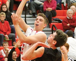 Girard's Jim Standohar shoots against Howland's Evan Steele during their game Tuesday in Girard. The Indians defeated the Tigers, 65-59.