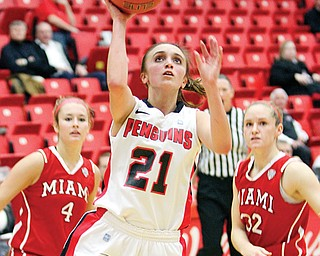 Youngstown State's Liz Hornberger shoots past Miami of Ohio defenders Maddie McCallie (4) and Hannah Robertson (32) during their game Wednesday at Beeghly Center. The Penguins fell to the RedHawks, 70-67, in the final minutes.