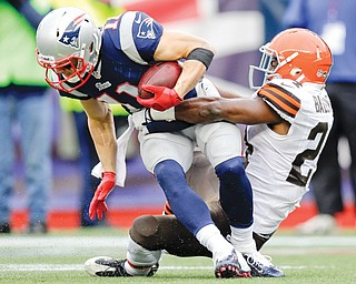 Cleveland Browns cornerback Johnson Bademosi, right, tackles New England Patriots wide receiver Julian Edelman after a catch in the second quarter of Sunday's game in Foxborough, Mass.