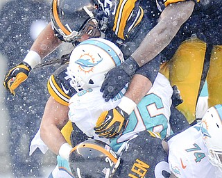 Miami Dolphins running back Lamar Miller (26) is tacked by Steelers inside linebacker Lawrence Timmons, top, defensive end Cameron Heyward and cornerback Cortez Allen during the second half of Sunday's game in Pittsburgh. Miami won 34-28.