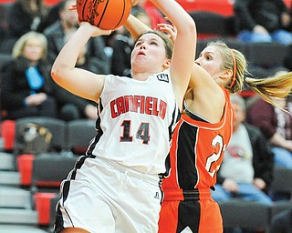 Canfield's Lynnae Whitehead (14) shoots after dribbling around Howland's Gabby Cvengros during Monday's game in Canfield. The Cardinals won the All-American Conference American Division game, 59-58.