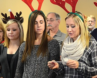 Ashley Kane, above left, Brittaney Zupko and Halle Smrek — all senior basketball players at Struthers High School — join the Struthers Rotary at Maplecrest Nursing Home to sing Christmas carols to residents. The five basketball players in attendance Tuesday afternoon donned festive reindeer antlers to help residents get in the holiday spirit. At top, Lisa Daprile, an owner of Maplecrest Nursing Home, joins in song with others from the Struthers Rotary.