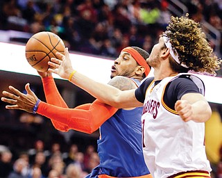 New York Knicks' Carmelo Anthony, center, grabs a rebound against Cleveland Cavaliers' Anderson Varejao of Brazil in the second quarter of an NBA game Tuesday in Cleveland.