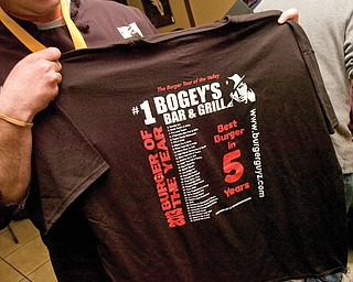 Chef McKee holds a T-shirt after receiving the Burger of the Year Award.