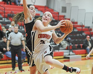Canfield's Rachel Tinkey (21) drives past Struthers' Brittaney Zupko on her way to the basket Thursday night. The visiting Wildcats beat the Cardinals, 60-57, in an All-American Conference, American Division game.