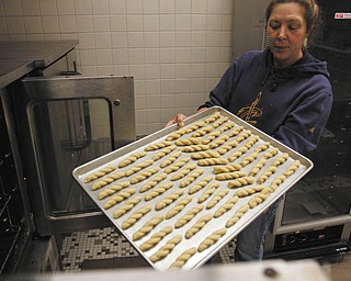 ROBERT K. YOSAY | THE VINDICATOR:  Dorothy Kippner places the koulourakia in an oven at St. John's Greek Orthodox Church on Glenwood Avenue., when the church women met recently to bake for their annual cookie fundraiser.