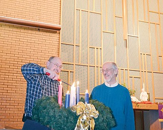 The Rev. Glenn Hamilton, left, pastor of Grace United Methodist Church in Warren, lights the Christ candle in the Advent wreath as he will do during a Longest Night Service planned at 7 p.m. Wednesday at his church. Watching is the Rev. Dr. Jim Ellison, pastor of Tod Avenue United Methodist Church in Warren, who will be among Methodist clergy joining together for the service of remembering and healing.