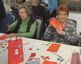 Special to The Vindicator: Residents of Whispering Pines Village in Columbiana recently enjoyed an afternoon of making Christmas crafts and their second annual bake sale. They raised more than $250, which will be donated to Toys for Tots. Resident crafters are Pernie Wukotich, left, and Donna Round.