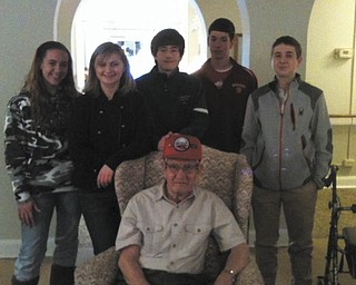Members of Holy Family Youth Ministry recently visited Blackburn, Sunrise and Greenbriar care facilities to honor residents who are veterans. Standing behind retired Sgt. George Henry of the U.S. Army Airborne Division are, from left, Courtney Conklin, Abbey Lea, Mark Stein, Jay Raymer and Robert Kurta. Henry is a resident of the Blackburn Home. HFYM is led by Maureen Kelty, director of religious education. Special to The Vindicator       SPECIAL TO THE VINDICATOR