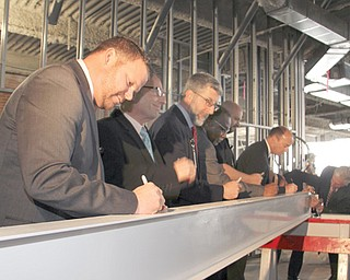 Kirk M. Ray, left, chief executive officer of ValleyCare Northside Medical Center, and others sign the topper steel beam during a topping-out ceremony Thursday at the hospital on Gypsy Lane in Youngstown.