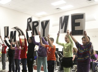 William D. Lewis The Vindicator Students at Girard IntermediAte School hold up cards spelling out Will You Marry Me? while 5 th grade teacher Joe Carbon proposes to fellow 5th grade teacher Alyssa DiBernardi during a 12-20-13 asembly at the school.