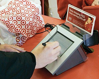 A customer signs his credit-card receipt at a Target store in Tallahassee, Fla. The U.S. is the juiciest target for hackers hunting credit-card information, and experts say incidents such as the recent data theft at Target's stores will get worse before they get better.