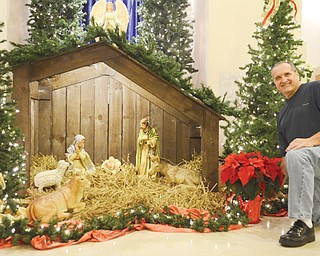 "Wes Scott, a member of St. Joseph the Provider Church in Campbell, sets a poinsettia plant next to the manger that is the focal point of the Christmas decorations at the church. He said the manger has a ""rough look"" to mimic a stable."