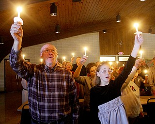 William D Lewis The Vindicator Jim Pence of Austintown and his grandaughter Grace Rusko, 11, of Canfield hold candles and sing Silent Night during Christmas Eve service at Western Reserve United Methodist Church in Canfield.
