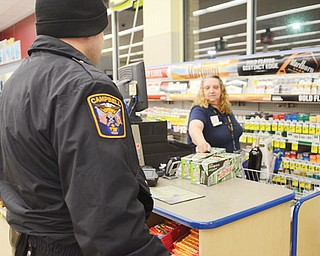 Campbell police officer Joe Pavlansky checks in with Rite Aid employee Cindy Stanovich. Pavlansky is part of the