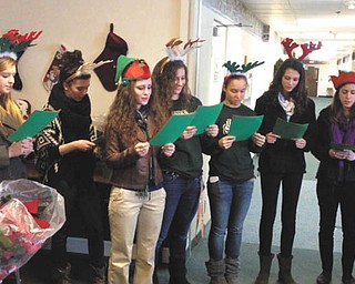 SPECIAL TO THE VINDICATOR The Ursuline High School softball team arrived with poinsettias and sang Christmas carols to deliver holiday cheer to the residents of Park Vista recently. From the left are some of Santa's reindeer and elves, Olexa Bunofski, Chelsea Kernan, Anny Carroll, Stephanie Ohalek, Megan Ross, Lorraine Fitzgerald and Leah Carroll.