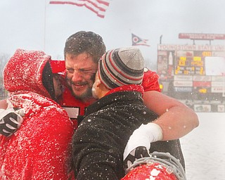 Youngstown State football player Fred Herdman (57) embraces his brother Justin Herdman, left, and father Fred Herdman Sr. after YSU's 42-13 loss to South Dakota on Nov. 23 at Stambaugh Stadium. It was the Penguins' final game of the season.