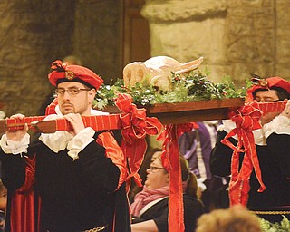 Jason Lisko, left, carries the boar's head with his brother, Josh, at Sunday's 53rd annual Boar's Head and Yule Log Festival at St. John's Episcopal Church in downtown Youngstown.