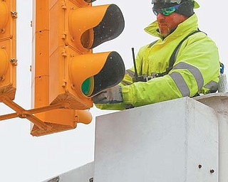Jimmy Clacko with the city of Youngstown's traffic engineers department replaces a burned out bulb on a traffic signal at Delason and Oak Hill avenues on the South Side. Clacko said a lot of lights burn out due to cold weather.