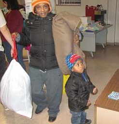 Kerrie Smith of Warren and her son leave the Salvation Army on Franklin Street with coats and other items they can use to get through the winter. They were among scores of people who came Monday morning to the giveaway, prompted by the bitter-cold temperatures coming to the Mahoning Valley this week.