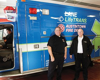 Austintown Fire Chief Andy Frost III, left, and Randy Pugh, vice president of Lane LifeTrans, stand by a new ambulance. LifeTrans has joined with the fire department to serve the Austintown community.