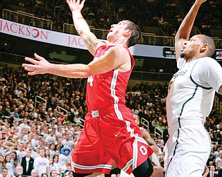 Ohio State's Aaron Craft puts up a layup against Michigan State's Adreian Payne during the first half of their NCAA basketball game Tuesday in East Lansing, Mich. The No. 5 Spartans edged the No. 3 Buckeyes, 72-68, in overtime.