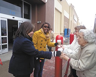 SPECIAL TO THE VINDICATOR The Brookdale Elves, seniors from Clare Bridge Austintown and Sterling House Youngstown, provided hot chocolate to Salvation Army bell-ringers from Dec. 4 at various times and locations through the holiday season. Jo for the Road provided the hot chocolate at a discount. Above, from left, are Taylor and Raven, Salvation Army volunteers working in front of Walmart in Austintown, who were served hot chocolate by elves Dorothy Thomas and Marguerite Cronin. Below, Salvation Army volunteer Heather, left, is receiving her hot chocolate from Thomas in front of Giant Eagle, also in Austintown.