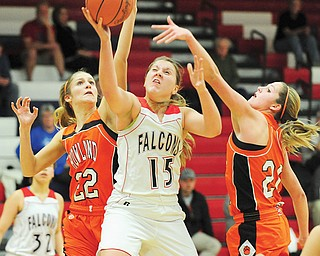 Howland 's Gabby Cvengros (22) and Sara Price (20) try to steal the ball off Fitch's Cassie Custer as she goes to the basket during the first half of their game Thursday in Austintown. The Falcons downed the Tigers, 65-41.