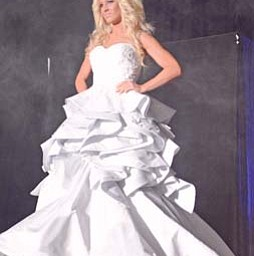 Krystal Naples walks the runway modeling a wedding gown from Evaline's Bridal shop of Warren during the bridal show at the Covelli Centre in Youngstown on Sunday afternoon.