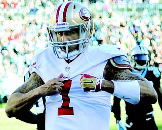San Francisco 49ers quarterback Colin Kaepernick pantomines ripping open his shirt after scoring a touchdown against the Carolina Panthers during the third quarter of the NFC divisional playoff game Sunday at Bank of America Stadium in Charlotte, N.C. The 49ers won 23-10 to advance to the NFC championship against the Seattle Seahawks this Sunday in Seattle.