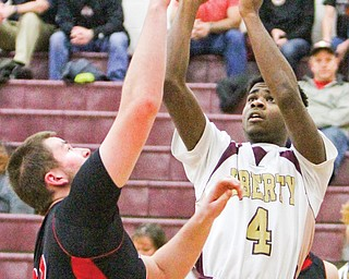 Liberty's Asim Pleas (4) shoots over Salem's Max Wolfgang during a game Tuesday in Liberty. Pleas scored 30 points, leading the Leopards over the Quakers, 73-67.