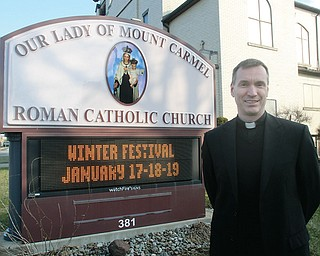 The Rev. John-Michael Lavelle, pastor of Our Lady of Mount Carmel Church, Niles, stands next to a sign promoting the winter festival this weekend. The church's summer festival, a tradition for more than 80 years, inspired the January event to satisfy those summer food cravings.