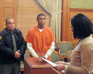 Taylor Ervin-Williams, center, listens as MaryJo Hoso, a victim-witness advocate in Trumbull County, reads a statement to Judge Ronald Rice. Standing next to Ervin-Williams is Deputy Dominic Massary. Judge Rice sentenced Ervin-Williams to 41 years in prison on kidnapping and robbery charges Wednesday.