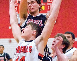 Campbell Memorial guard George Billiris grabs a rebound over the head of Canfield forward Mason Mangapora during the third quarter of their game Tuesday at Canfield High School. The Cardinals downed the Red Devils, 77-59. Canfield outre bounded Campbell, 41-26, and was more successful at free throws — 26 overall on 36 attempts.