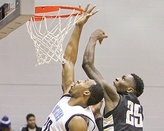 East's Terrell McLain puts up a shot while Warren Harding's Shondell Jackson defends during their game Tuesday at East High School. The Raiders routed the Panthers, 83-53.
