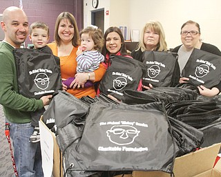 """Posing with school-supply bags to be distributed to students in Campbell City Schools are members of The Michael """"Mickey"""" Soroka Charitable Foundation, from left, Eric Gonzalez, holding son, Gavin, 4; Carmel Gonzalez, Eric's wife, holding their daughter, Elena, 1; Jennifer Kavouras, Rena Regula and Andrea McGoogan. Foundation members gathered Wednesday to fill bags to be distributed district wide Friday, weather permitting. The foundation was founded to carry on the legacy of Soroka, a Campbell High School teacher who went out of his way to help students whether they were enrolled in his classes or not. Soroka died in 2011 at age 49."""