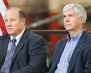 Detroit Mayor Mike Duggan, left, and Gov. Rick Snyder listen to a speaker at the IDEAL Group on Thursday in Detroit. Snyder announced a plan to ask the Obama administration to set aside thousands of work visas to entice talented immigrants to live and work in bankrupt Detroit. The Republican governor said he is seeking 50,000 work visas solely for the city over five years.