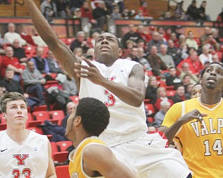 Youngstown State's Kendrick Perry puts up a layup over Valparaiso defender Lexus Williams during their game Thursday at YSU's Beeghly Center. Perry was one of four Penguins in double digits, but YSU fell, 74-71, to the Crusaders.