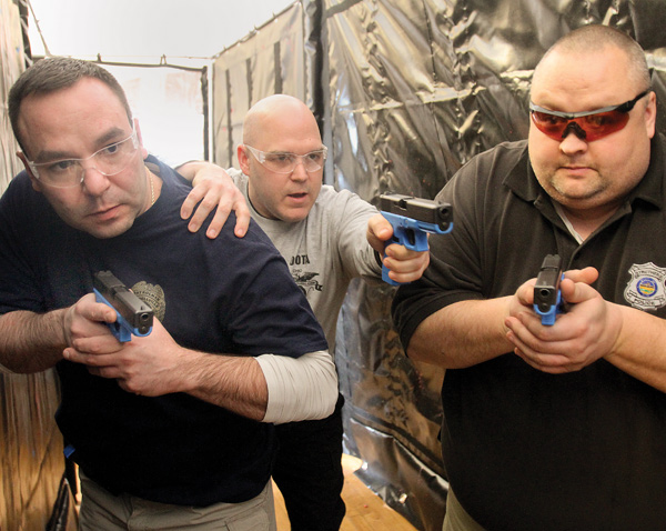 Bob Richardson, center, works with Sgt. Don Coppola of the Lowellville Police Department, left, and patrolman Patrick Campbell of the Struthers Police Department during an eight-hour law enforcement training session at Lowellville City Hall on Tuesday. Richardson, a law enforcement training officer with the Ohio Peace Officer Training Academy, was one of two instructors at the session, which was intended to help officers more safely and efficiently conduct building searches.