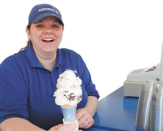 Austintown Handels Ice Cream employee Jen McNatt gets a cone ready for a customer. Despite the deep freeze, the ice-cream shop remains open to serve loyal customers.
