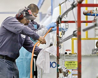 Employees at Sheffield Platers Inc. work on the factory floor in San Diego. A government report released Thursday showed consumers fueled solid economic growth in the final quarter of 2013.