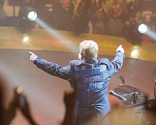 "Elton John points up at fans in the upper level of the arena after playing his second song, ""Bennie and the Jets,"" at the Covelli Centre concert. He was wearing a bedazzled blue jacket bearing the title of one of his songs, ""Madman Across the Water."""