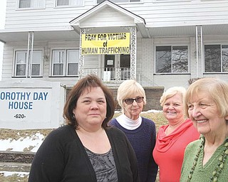 A banner at the Dorothy Day House of Hospitality, 620 Belmont Ave., Youngstown, promotes prayer for victims of human trafficking. A vigil will start at midnight Friday and continue through Saturday to raise awareness about the issue. Promoters of the event are, from left, Vicki Vicars, Mary Grace Manning, Valerie Seaborn and Ceil Schlosser.