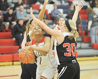 Fitch's Aaliyah Sadler goes to the basket against Struthers defenders Ashley Kane (30) and Halle Smrek (32) during the second quarter of Thursday's game at Fitch High School in Austintown. The Falcons downed the Wildcats, 52-45