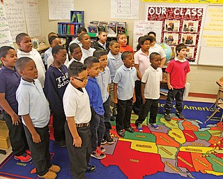 Laurie McEwan's fourth-grade class, above, performs the school song Monday. Each class will sing the song, and a panel of judges will narrow down the competition until a winner is identified.